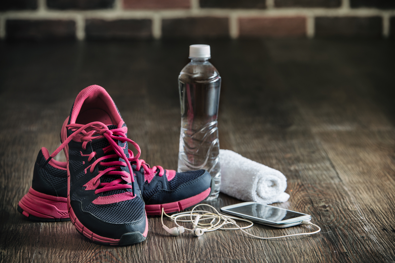 Running Shoes next to bottle of water, towel, and ear pods.