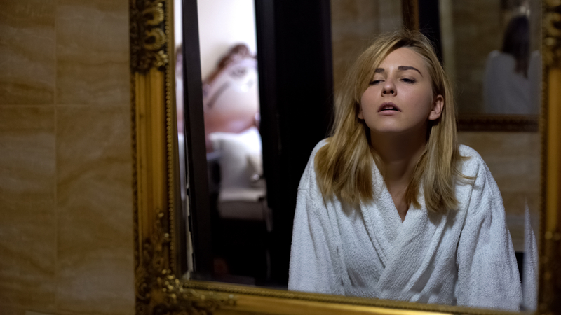 A women feeling nausea from a hangover looking in her bathroom mirror