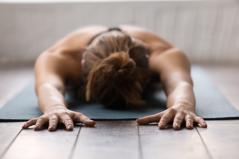 young woman practicing yoga, face down