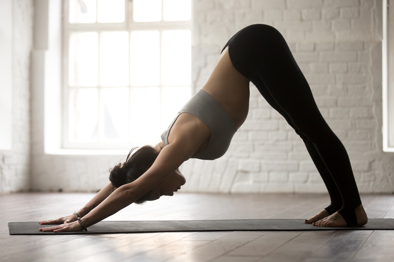 a young woman doing yoga pose downward facing dog